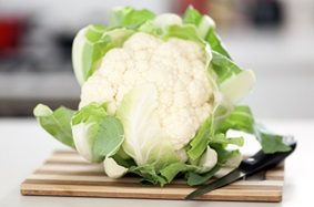 Whole cauliflower on cutting board with knife