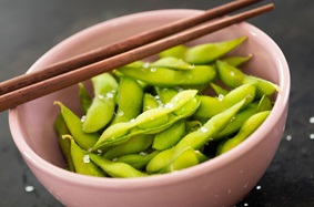 Edamame pods in a pink bowl with chopsticks
