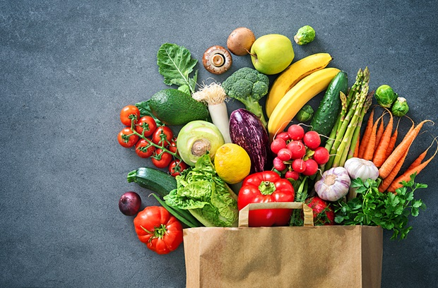 Fruits and vegetables spilling out of a paper shopping bag onto a slate background