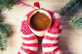 Gloved hands holding a mug of hot chocolate