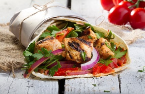 Grilled chicken wrap with onions, lettuce and tomatoes