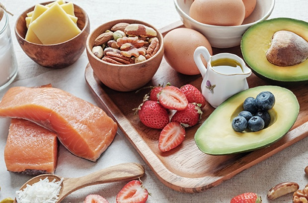 cheese_in_bowl_nuts_in_bowl_eggs_sliced_avocado_blueberries_strawberries_salmon_coconut_healthy_fats_for_keto_diet