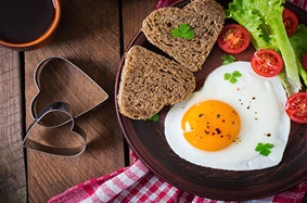 eggs and toast shaped like hearts on a plate