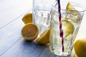 Water with lemon in clear glass with red and white straw