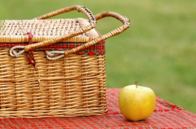 a picnic basket next to an apple on a table cloth