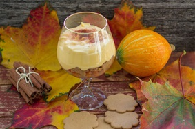 pumpkin mousse in a wine glass on a table with leaves