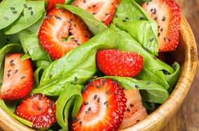 Bowl of strawberry, spinach greens and sesame seeds