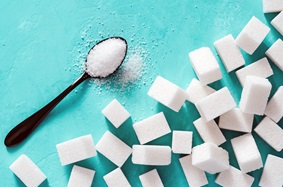 Spoon filled with granulated sugar surrounded by sugar cubes