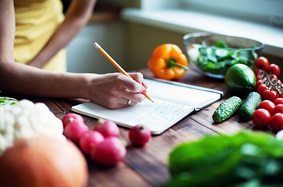 Woman writing in food journal surrounded by vegetables