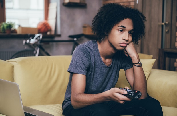 a bored looking boy sitting on the couch and holding a remote