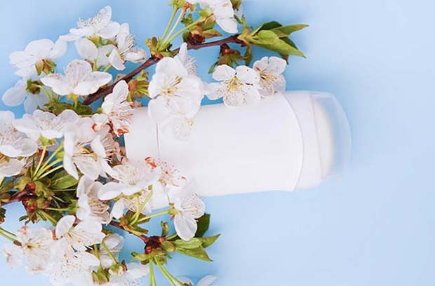 white_stick_of_deodorantlays_on_pale_blue_background_with_small_light_pink_flowers