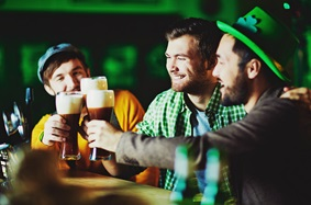guys wearing saint Patrick's day clothes while drinking beer