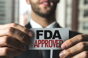 "Man holding a sign that says ""FDA approved"""