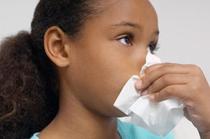 Young girl holding a tissue to her nose