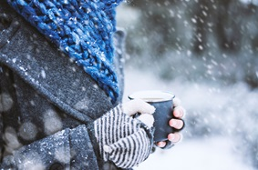 Person wearing gloves and a scarf, holding a mug, in the snow