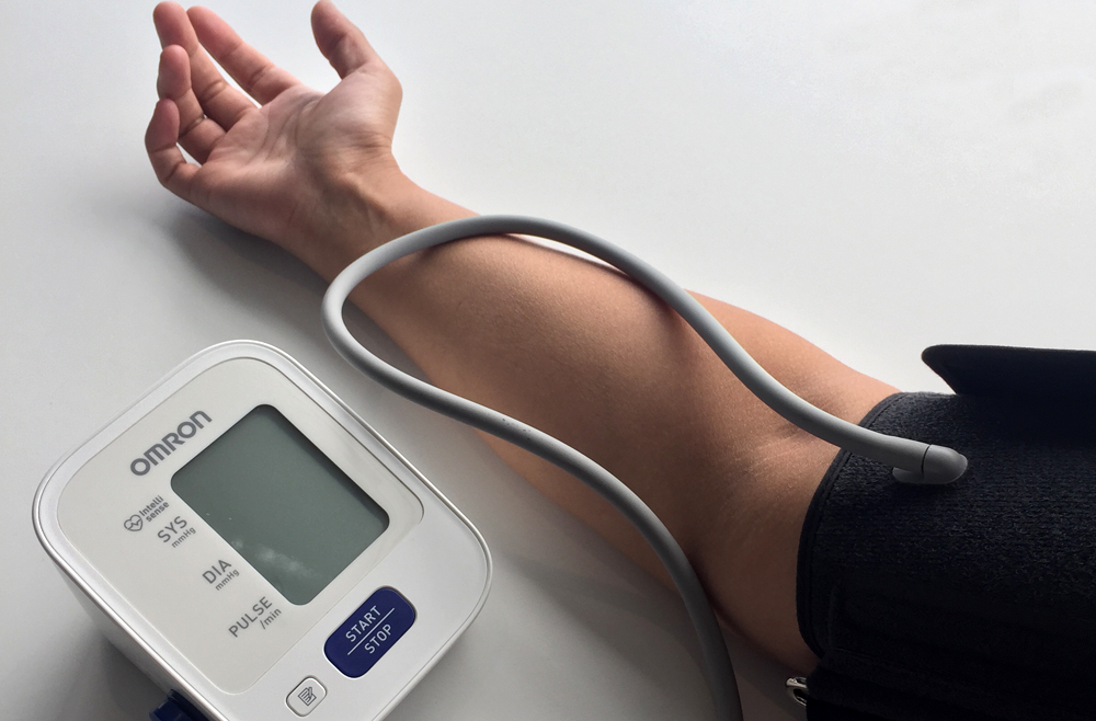 A woman taking her blood pressure using a digital blood pressure cuff