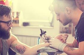 man getting a tattoo on his arm