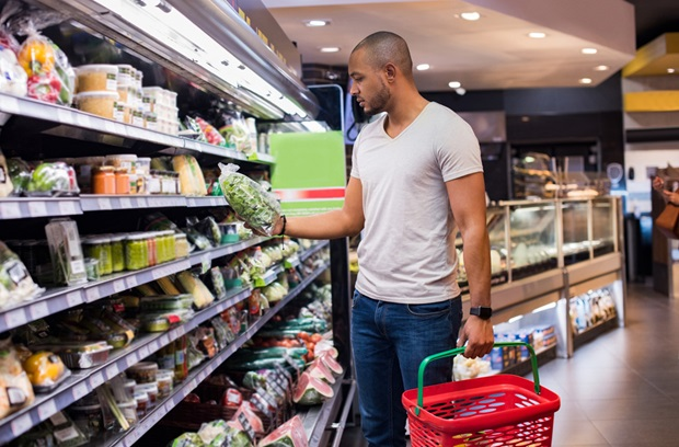 man looking at bag a of lettuce in a grocery store