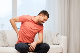 young adult male holds his left side while wincing in pain sitting on a white couch