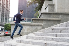 man in nice clothes running up cement steps