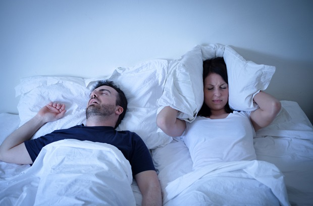 man snoring while in bed with a woman who is covering her head with a pillow