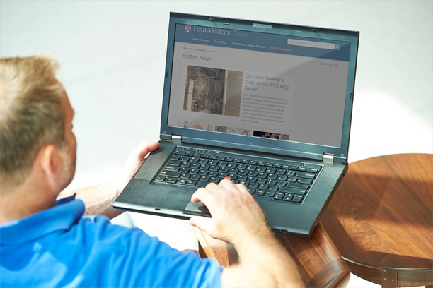 Man using PC laptop checking Penn Medicine News