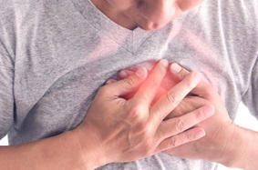 Man holding hands over chest in pain