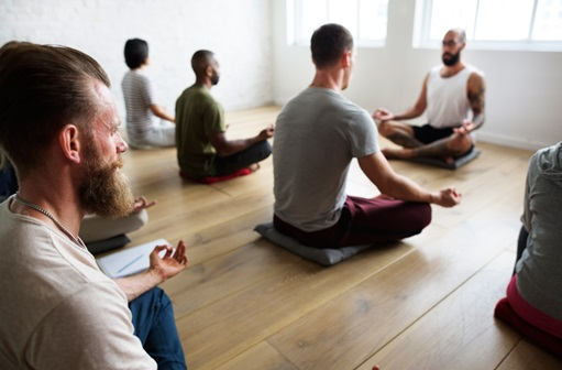group of people meditating in a room