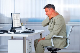 man holding neck while sitting at desk