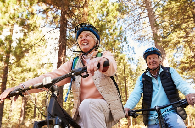 an older man and woman biking together in the Fall