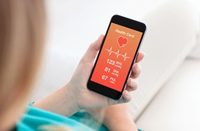 Woman holding a smartphone with app for heart monitoring