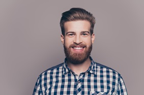 a man with a beard smiling and wearing a plaid shirt