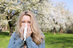 woman blowing her nose with blossoming trees in the background