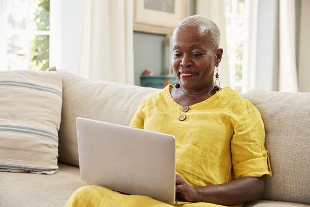 Mature woman sitting on a couch while using a laptop.