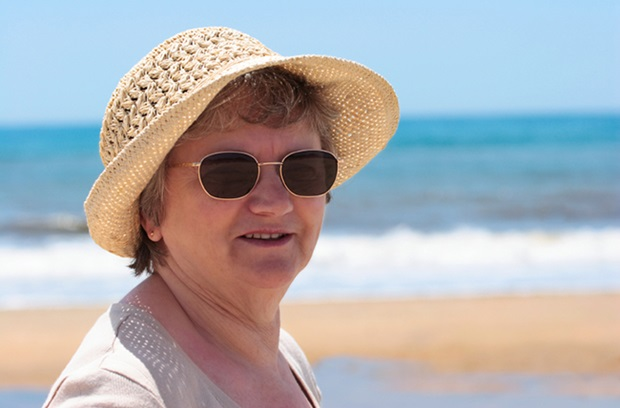 Older lady wearing hat and sunglasses at the beach