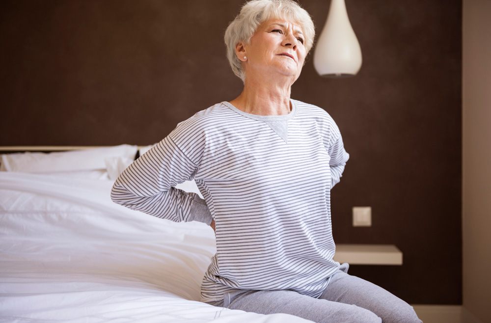 woman holding back in pain while sitting in bed