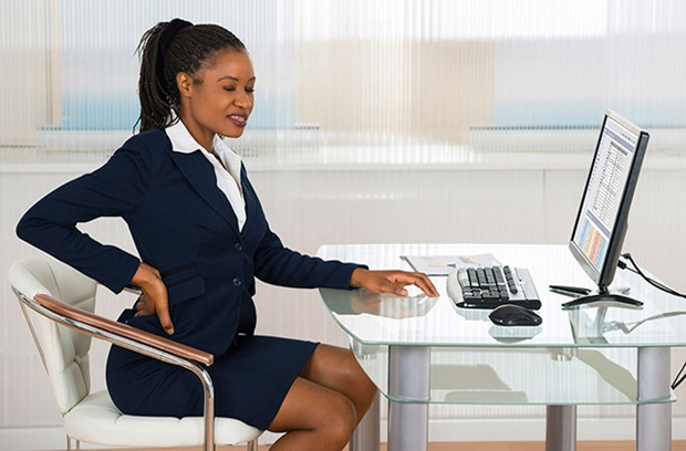Woman holding her lower back while sitting at a desk