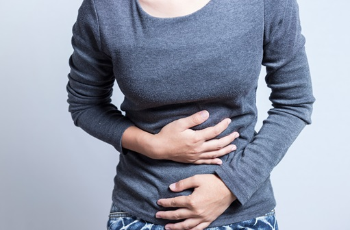 woman holding stomach, seemingly in pain