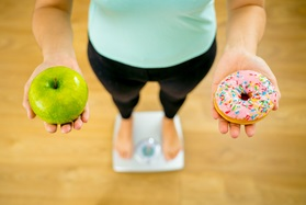 Woman standing on scale holding an apple and a doughnut