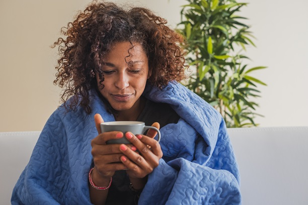 Sick woman wrapped in blanket holding a mug