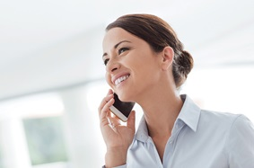 woman smiling and talking on cell phone