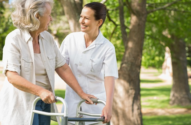 woman using a walker while another woman helps