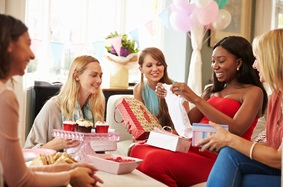 a group of women watching one woman open presents at a baby shower