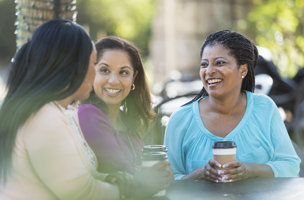 3 women talking over coffee at an outside table