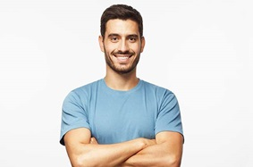 middle_aged_man_black_hair_facial_hair_folds_arm_smiles_wearing_blue_shirt
