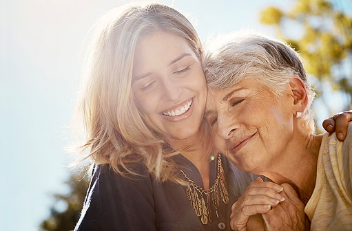A grandmother hugging her adult granddaughter while smiling