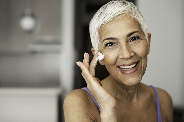 Mature woman applying wrinkle cream to her face