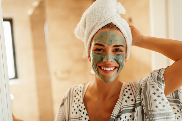 Smiling woman wearing a green beauty mask.