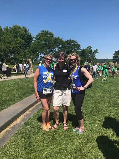 Tracey outside with her friends Arianna and Kristy wearing sarcoma awareness t-shirts at a race for awareness for sarcoma