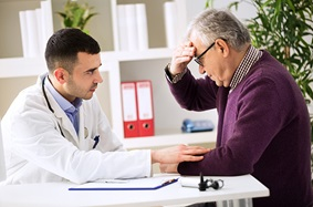 man holding head while sitting across from male doctor